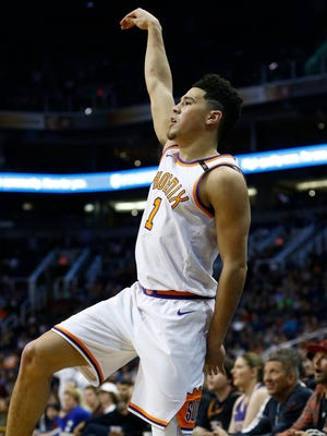 Phoenix Suns guard Devin Booker watches a 3-pointer go in during the first half of an NBA basketball game against the Memphis Grizzlies, Tuesday, Dec. 26, 2017, in Phoenix.