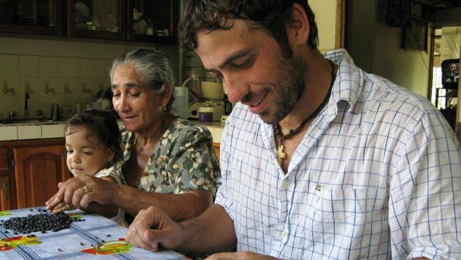 Peace Corps volunteer Mick Wigal, 29, of Youngstown, Ohio, sorts beans with his host family in Caño Nego, Costa Rica on Sept. 11, 2010.
