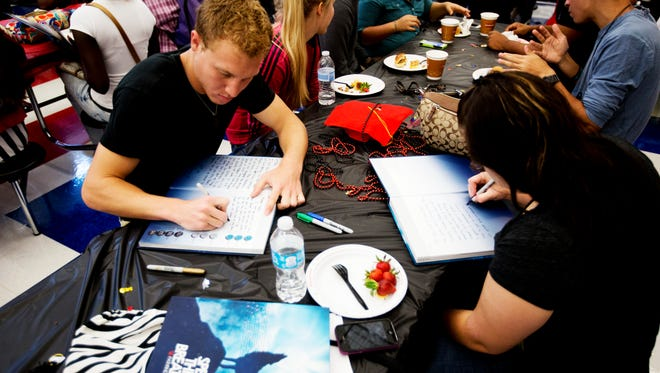 South Fort Myers High School students, Dillon Pruskauer and Cortnee Bates sign traditional yearbooks.