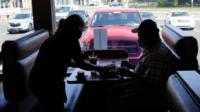 A waitress serves lunch to a customer at the Penrose Diner, Tuesday, Sept. 8, 2020, in Philadelphia.
