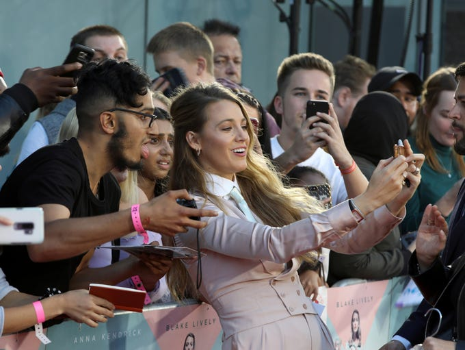 Actress Blake Lively poses with fans upon arrival at