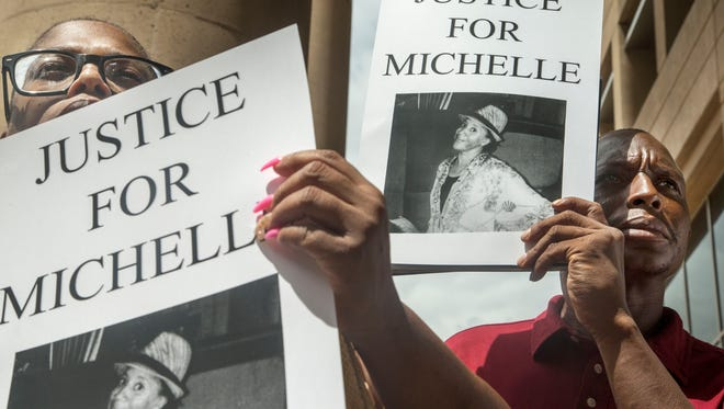Protesters hold posters featuring images of Michelle Cusseaux at a Aug. 18 press conference at Phoenix City Hall.