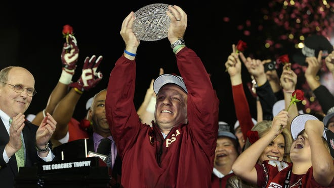 Florida State coach Jimbo Fisher hoists the Coaches' Trophy after defeating Auburn in the 2014 BCS National Championship Game.
