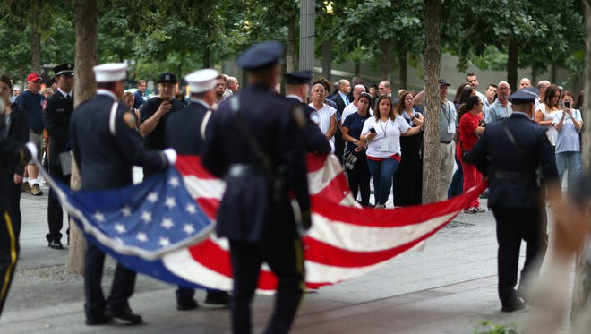 NYPD and FDNY officers bring in the American flag during memorial observances on the 13th anniversary of the Sept. 11 terror attacks on the World Trade Center in New York, Thursday, Sept. 11, 2014.   Family and friends of those who died read the names of the nearly 3,000 people killed in New York, at the Pentagon and near Shanksville, Pennsylvania. (AP Photo/The New York Times, Chang W. Lee, Pool)