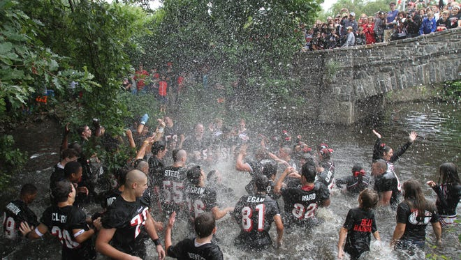Rye players celebrate their 24-13 victory over Harrison with a jump in the river as fans cheer from bridge.