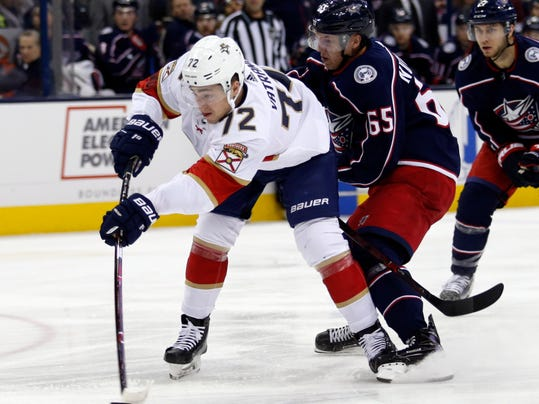 Florida Panthers forward Frank Vatrano, left, takes a shot in front of Columbus Blue Jackets defenseman Markus Nutivaara, of Finland, during the first period of an NHL hockey game in Columbus, Ohio, Thursday, March 22, 2018. (AP Photo/Paul Vernon)