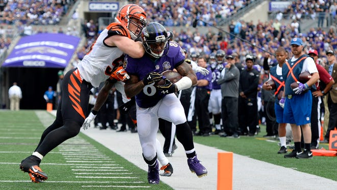 Cincinnati Bengals outside linebacker A.J. Hawk (50) drives Baltimore Ravens wide receiver Steve Smith (89) out of bounds during the fourth quarter at M&T Bank Stadium.