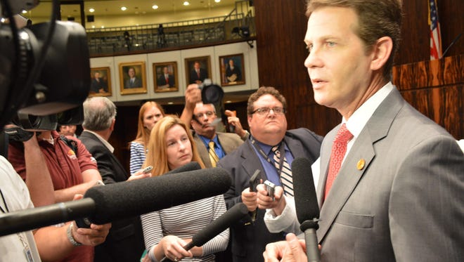 Senate President Andy Gardiner, R-Orlando, talks with reporters after a Senate session.
