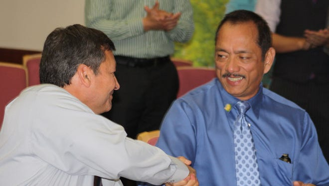 In this March 9, 2011, file photo, Gov. Eddie Calvo, left, shake hands with then-Vice Speaker Benjamin Cruz after signing two bills.