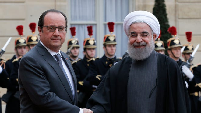 French president Francois Hollande, left,  greets Iranian President Hassan Rouhani before a meeting at the Elysee Palace, in Paris, Thursday, Jan. 28, 2016.