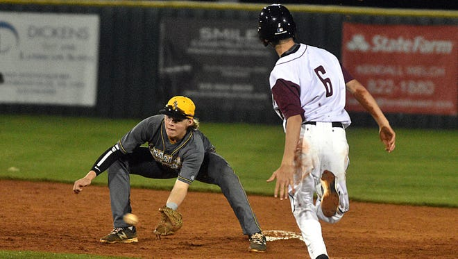 Hendersonville junior shortstop Brett Coker fields a throw as Station Camp's Grant Jones attempts to steal second base during Monday's game.