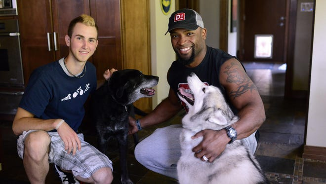 Former Green Bay Packers star Ahman Green found Luke, a 13-year-old black Lab, in his Ledgeview kitchen after the dog came in through the doggy door in the background. Green returned him to owner Jesse Belleau, left, 17. Green is holding one of his three dogs, Nanook.