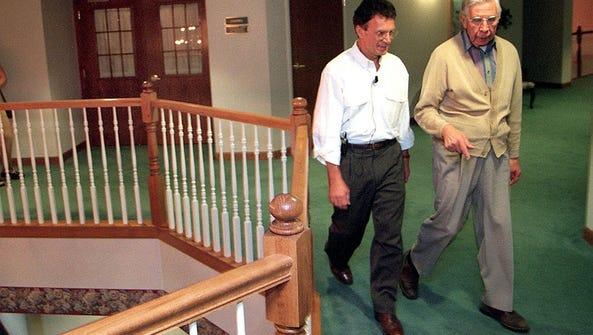 Sen. Tom Daschle walks with resident Roger Fredrikson