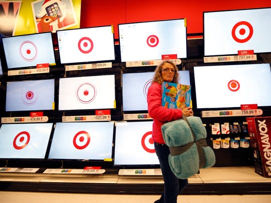 In this Nov. 28, 2014, file photo, a customer walks past a bank of flat screen televisions at a Target store in South Portland, Maine. Target Corp. reports earnings Wednesday, Nov. 15.