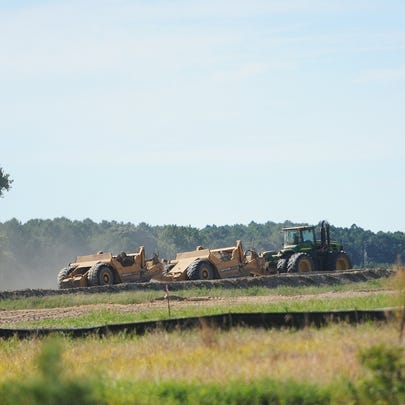 Heavy equipment preps the site of a planned poultry