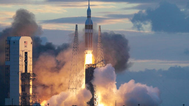 A NASA Orion capsule on top of a Delta IV rocket lifts off on its first unmanned orbital test flight from Cape Canaveral Air Force Station on Dec. 5
