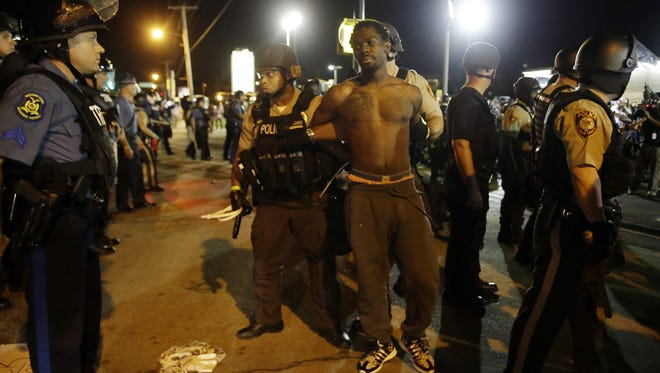 St. Louis County Police make an arrest along West Florissant Avenue, Aug. 10, 2015, in Ferguson, Mo.