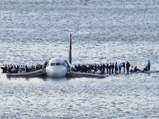In this Thursday Jan. 15, 2009 file photo, airline passengers wait to be rescued on the wings of a US Airways Airbus 320 jetliner that safely ditched in the frigid waters of the Hudson River in New York, after a flock of birds knocked out both its engines. The audio recordings of US Airways Flight 1549, released Thursday, Feb 5, 2009 by the Federal Aviation Administration, reflect the initial tension between tower controllers and the cockpit and then confusion about whether the passenger jet went into the river. (AP Photo/Steven Day) ** EDITORS NOTE RESTRICTIONS: TO USE THIS IMAGE IN AN EDITORIAL MAGAZINE, PLEASE CONTACT YOUR AP IMAGES LICENSING REPRESENTATIVE. SPECIAL RATES APPLY **