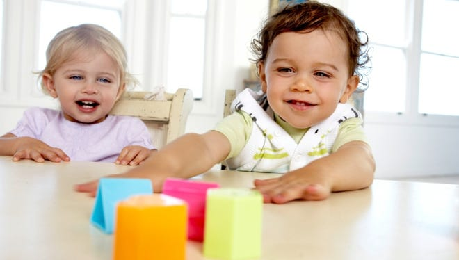 Baby boy and girl sitting at table playing with colorful blocks.