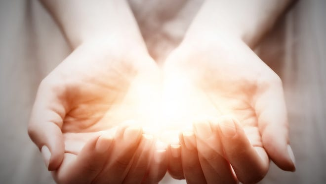 The light in young woman hands in cupped shape.