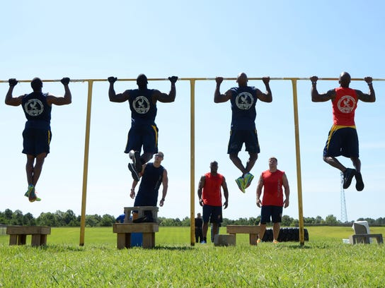 Members of the Mississippi Highway Patrol's fitness team do chin-ups at the Mississippi Law Enforcement Officers Training Academy in Pearl, Mississippi on Wednesday, July 1, 2015.