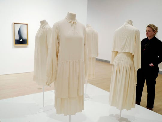 """In this March 16, 2017 photo, visitors to the Brooklyn Museum in New York look at tunics worn by artist Georgia O'Keeffe. The exhibit, """"Georgia O'Keeffe: Living Modern"""" highlights her role as a style icon."""