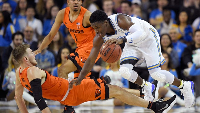 UCLA guard Aaron Holiday, right, knocks over Oregon State forward Tres Tinkle, left, as guard Stephen Thompson Jr. watches during the first half of an NCAA college basketball game Thursday, Feb. 15, 2018, in Los Angeles.