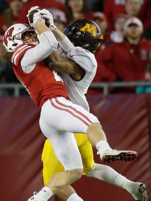 Minnesota running back Rodney Smith comes down with a 25-yard reception despite the efforts of Wisconsin safety Leo Musso during the third quarter.