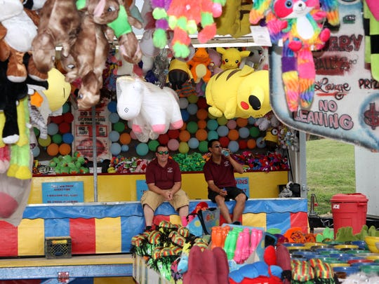 Employees of Moore's Greater Shows put the finishing touches on the carnival before opening Wednesday evening.
