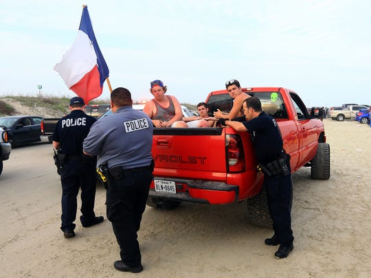Police officers from Port Aransas Police Department and other area agencies inspect a pickup after a fight broke out during spring break Tuesday, March 15, 2016, in Port Aransas.