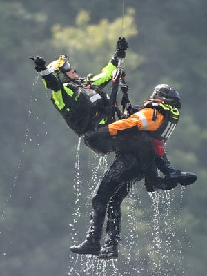 A member of the Pennsylvania Helicopter Aquatic Rescue Team gives a thumbs up as he and a member of the Pennsylvania Fish and Boat Commission are hoisted up into a Blackhawk helicopter. The duo were participating in a water rescue simulation at Lake Williams in conjunction with local water rescue companies on Saturday, August 20, 2016.