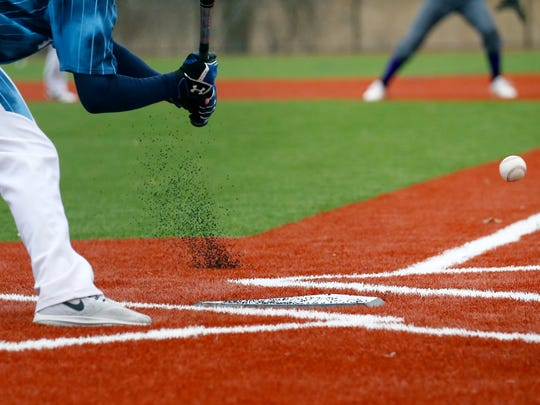 Rubber pellets fly out of the surface of the turf in front of a batter in the second inning of a game at Eastridge High School. The Lancers have a brand new all-turf baseball field, the first of its kind at a Monroe County high school.