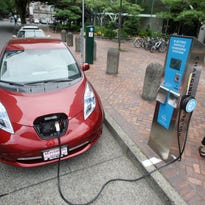 A Nissan Leaf charges at a electric vehicle charging station in Portland, Ore.