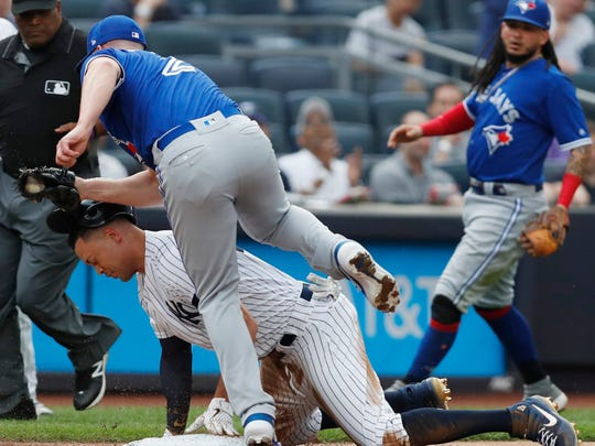 Toronto Blue Jays starting pitcher Clayton Richard (2) steps over New York Yankees' Giancarlo Stanton after tagging Stanton out at third on a double play during the first inning of a baseball game, Tuesday, June 25, 2019, in New York. Stanton left after the third inning. Blue Jays shortstop Freddy Galvis backs up the play, right. Umpire Laz Diaz is at left rear. (AP Photo/Kathy Willens)
