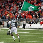 Michigan State Spartans running back Delton Williams (22) celebrates with a school flag after the Spartans' game against the Ohio State Buckeyes at Ohio Stadium. The Spartans won 17-14.