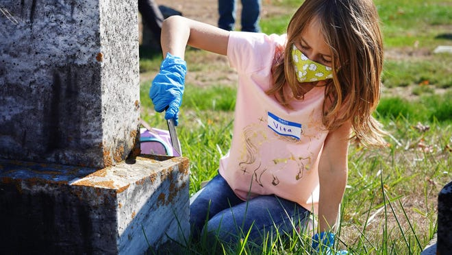 Third-grader Vita and other students at the Coastal Ridge Elementary School students clean gravestones Thursday at First Parish Cemetery in York.