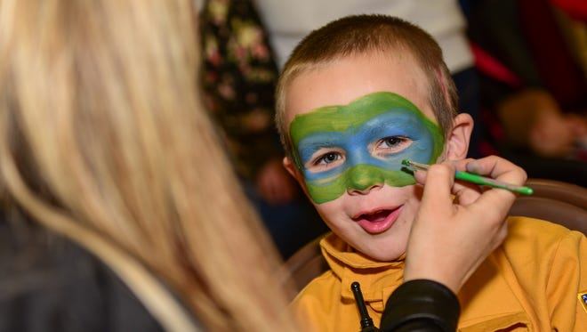 J.C. Dotson, 5, of Grimes, has his face painted during the town's Halloween Fest last year. Grimes is the fourth happiest small town in America, according to a new list