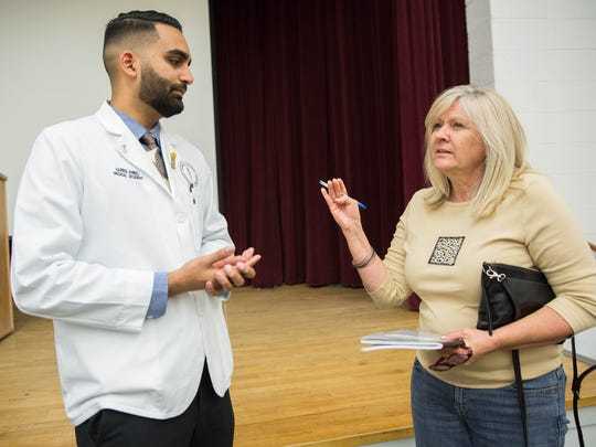 Harris Ahmed, left, talks with Bev Courtney, right, after the David Horowitz speech Wednesday May 3, 2017 at Gerald Thomas Hall at New Mexico State University. Ahmed and Courtney discussed Horowitz's speech.