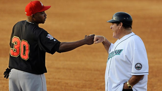 Pete Rose fist bumps with the Lancaster Barnstormers' Wilson Batista on Monday. Rose, guest manager of Bridgeport, also coached first base.