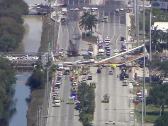 In this frame from video, emergency personnel work