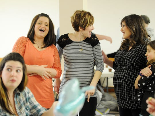 ERIN McCRACKEN / COURIER & PRESSSara McCarter (left), her best friend, Kerri Lane, (center) and her surrogate, Tara Pearce, (right) enjoy each other's company at McCarter's baby shower  at St.Vincent Catholic Church in Vincennes, Ind., on Feb. 7, 2015. Lane and McCarter have enjoyed being pregnant together, even though McCarter is not carrying her babies. Lane has tried to make sure that McCarter enjoys all the little moments of pregnancy and preparing for her children. Lane gave birth to a baby boy the Sunday after the shower.
