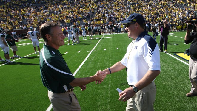 Michigan State head coach Mark Dantonio, left, and  Michigan head coach Rich Rodriguez greet each other at midfield as the teams warm up before their game in Ann Arbor on Oct. 9, 2010.
