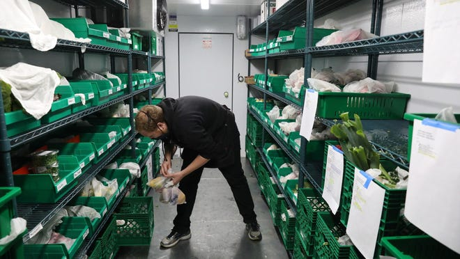 Joe Buhnerkempe organizes fruits and vegetables in a walk-in cooler on Oct. 23, 2020 at Village Farmstand in Evanston, Illinois.