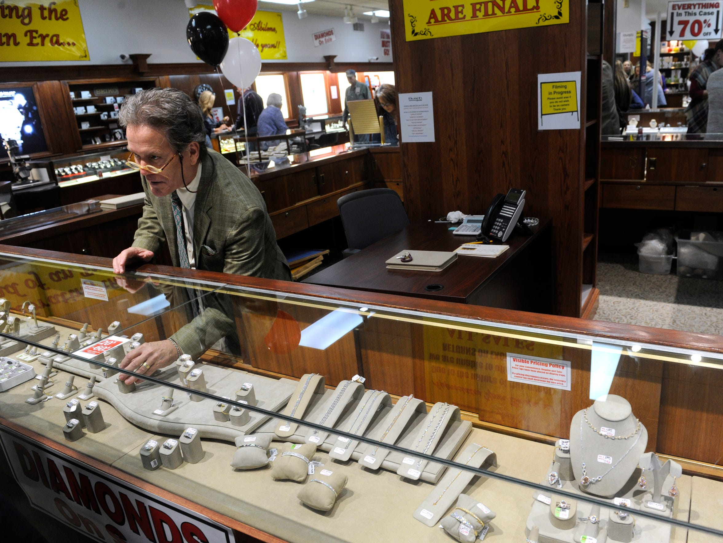 Owner Don Fite reaches into a case at Busch Jewelers