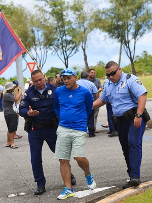Protester Harold Cruz is led away in handcuffs by Guam Police Department officers after he and other protesters blocked traffic exiting Andersen Air Force Base during a peaceful demonstration outside the military complex in Yigo on Saturday, Sept. 23, 2017.