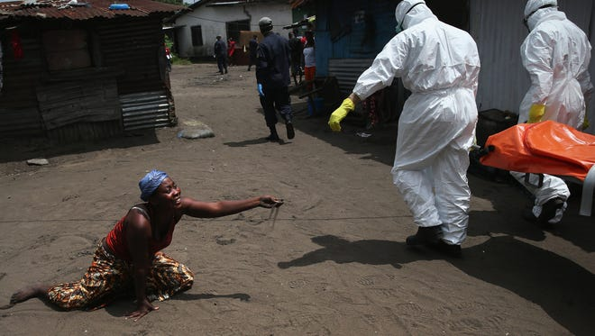 A woman throws a handful of soil toward the body of her sister as Ebola burial team members take her for cremation Friday in Monrovia, Liberia.
