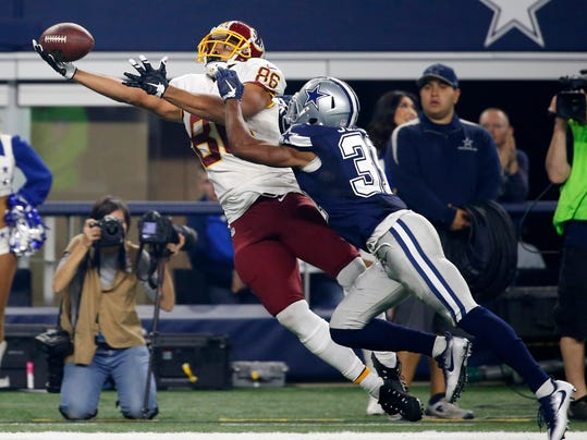 In this Nov. 24, 2016, photo, Washington Redskins tight end Jordan Reed (86) lays out to catch a pass in front of Dallas Cowboys' Byron Jones (31) during the second half of an NFL football game in Arlington, Texas. Reed says he has a Grade 3 sprain of the AC joint in his left shoulder. Reed did not practice Nov. 28 and is taking it day by day and not ruling himself out to play Sunday at the Arizona Cardinals. He injured his shoulder in the Redskins' 31-26 loss to the Dallas Cowboys on Thanksgiving and had an MRI Friday. (AP Photo/Michael Ainsworth)