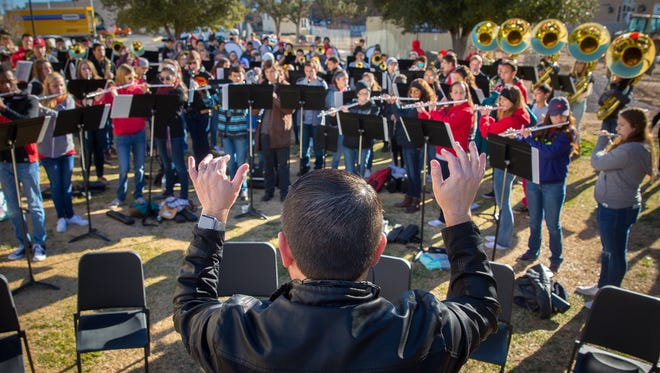 "Centennial High School Band Leader Joseph Flores conducts the band in a rendition of ""Louie Louie"" at the Farmers & Crafts Market Saturday Morning. The Centennial Band conducted a 12 hour music marathon at the market, Mesilla Plaza and the Pan American Center during a NMSU basketball game to raise money for the school's music program."