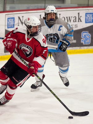 Champlain Valley's Jake Schaefer, left, tries to clear the zone ahead of South Burlington's Dylan LeClair during Saturday's CSB Cup boys hockey game at Cairns Arena in South Burlington.
