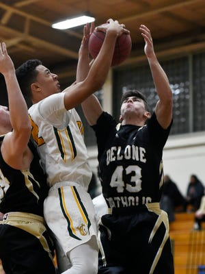 York Catholic's Eric Phelps and Delone Catholic's Shamus Keefe fight for the rebound in the first half of a YAIAA boys basketball game Friday, Jan. 5, 2018, at York Catholic. York Catholic defeated Delone Catholic 70-36.